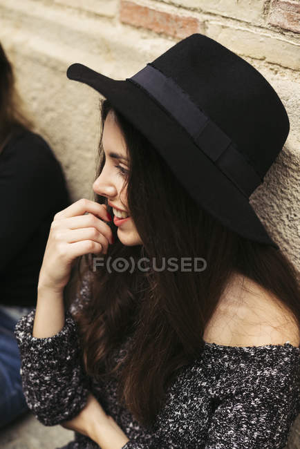 Smiling young woman wearing black hat — Stock Photo