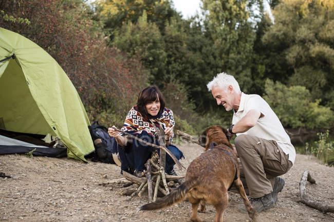 Coppia anziana con cane in una tenda che prepara un falò — Foto stock