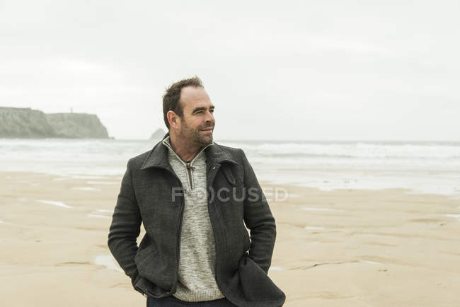 Smiling man walking on the beach with hands in pockets — Stock Photo