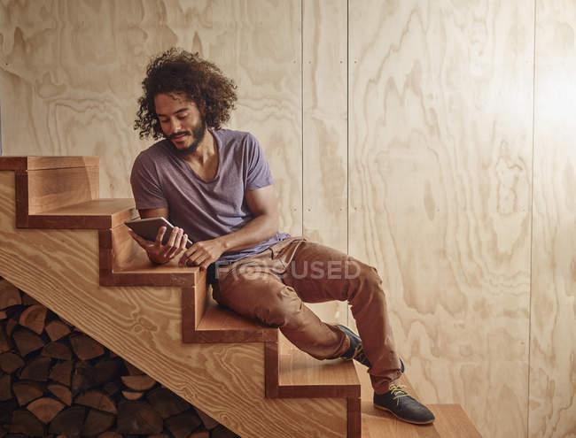 Jovem em escadas de madeira olhando para tablet digital — Fotografia de Stock
