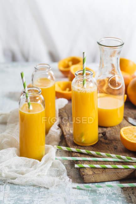 Laranjas fatiadas e garrafas de vidro de suco de laranja espremido na hora — Fotografia de Stock