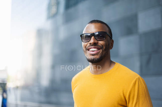 Portrait of smiling man wearing yellow pullover and sunglasses — Stock Photo