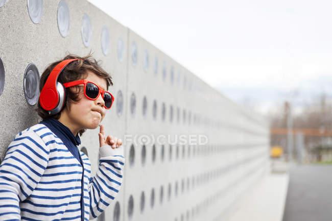 Portrait de petit garçon portant des lunettes de soleil écoutant de la musique avec des écouteurs — Photo de stock