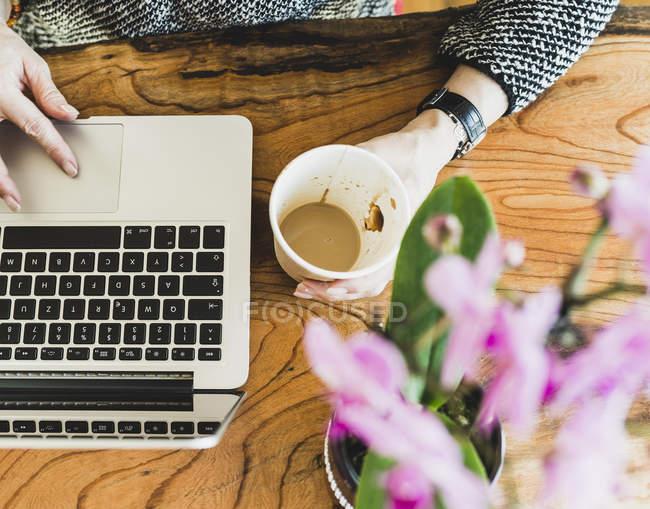 Крупный план женщины с кофе и ноутбуком за столом — стоковое фото