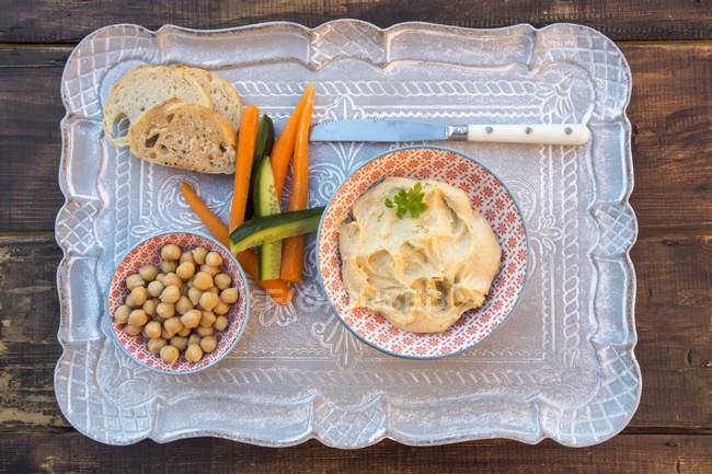Хумус, горох, морква, огірок, багет на лоток — стокове фото