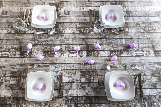 Vier Gedecke am gedeckten Tisch mit Osterdekoration — Stockfoto
