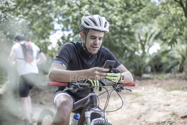 Man on mountain bike in forest using cell phone — Stock Photo