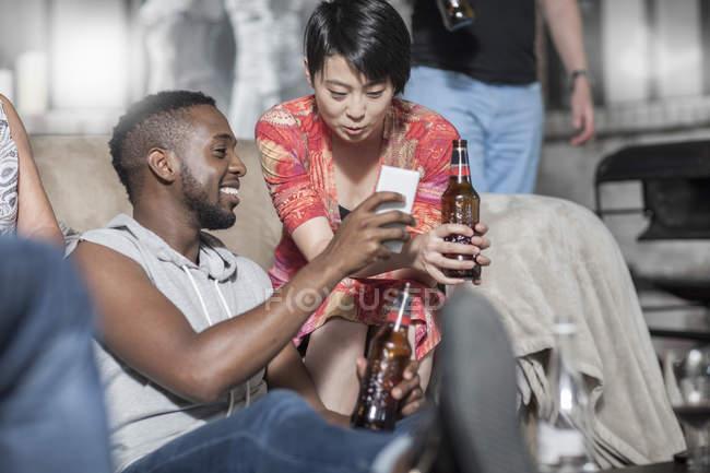 Amigos com garrafas de cerveja compartilhamento celular na festa — Fotografia de Stock