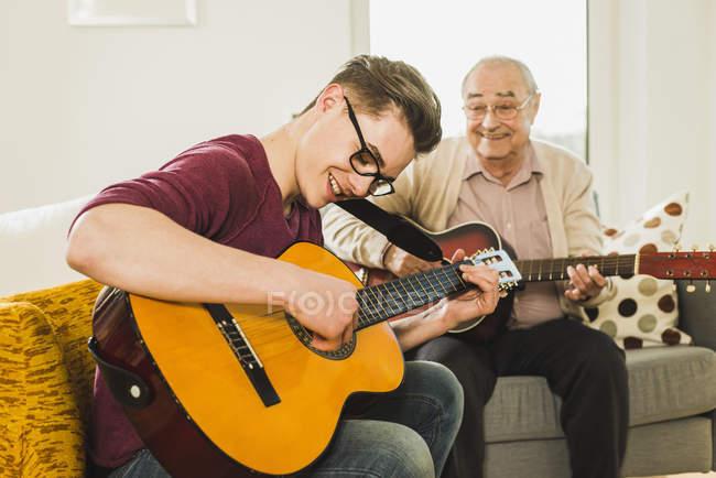 Abuelo y su nieto tocando juntos la guitarra - foto de stock