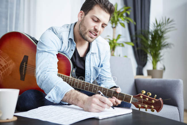 Young man with guitar composing a song — Stock Photo