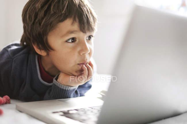 Retrato de um menino olhando para o laptop — Fotografia de Stock