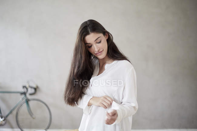 Молодая женщина закатывает рукав блузки — стоковое фото