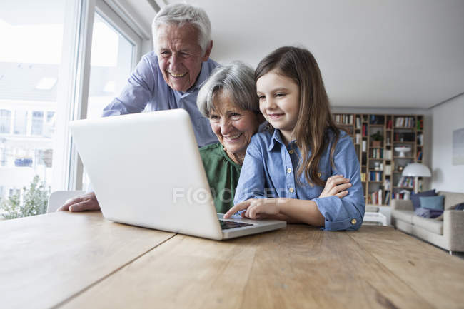 Grandparents and their granddaughter with laptop at home — Stock Photo