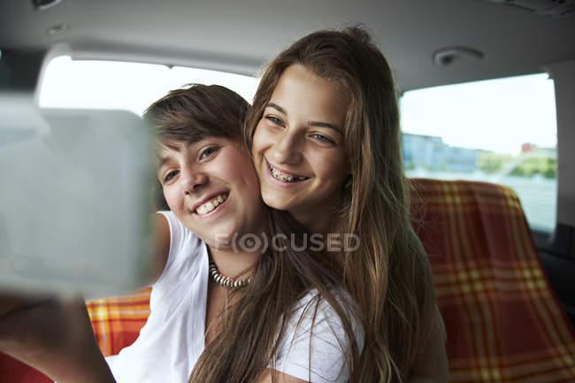 Two teenage girls taking a selfie in car — Stock Photo