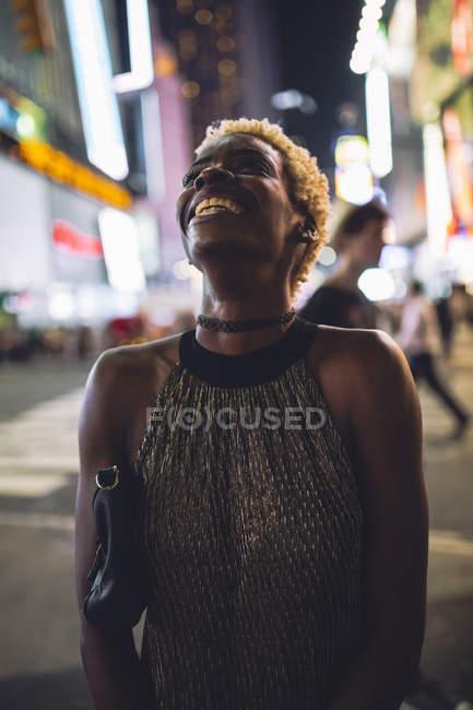 Retrato de uma jovem feliz e bem vestida na Times Square à noite, Nova Iorque, EUA — Fotografia de Stock