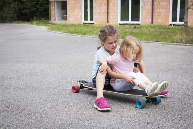 Two sisters sitting on longboard outdoors — Stock Photo