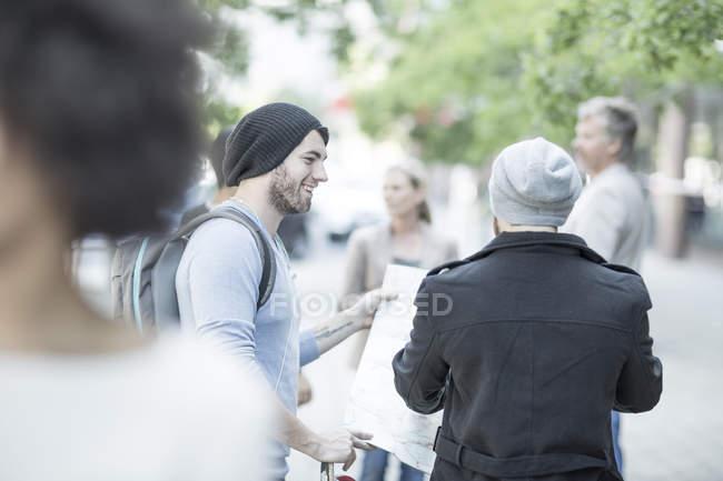 Молодые люди в городе с картой, ищет направления — стоковое фото