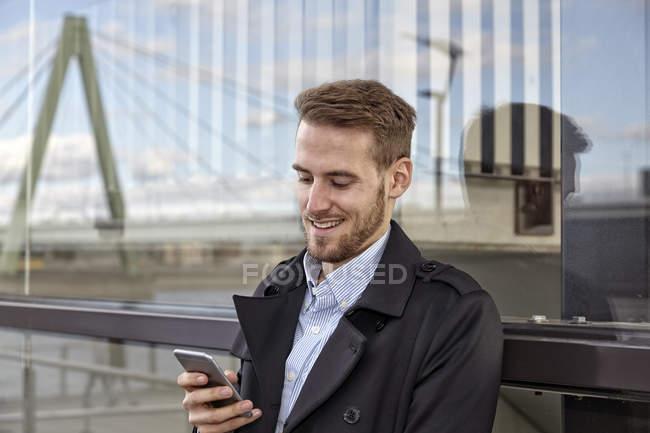 Sorridente giovane uomo utilizzando il telefono cellulare all'aperto — Foto stock