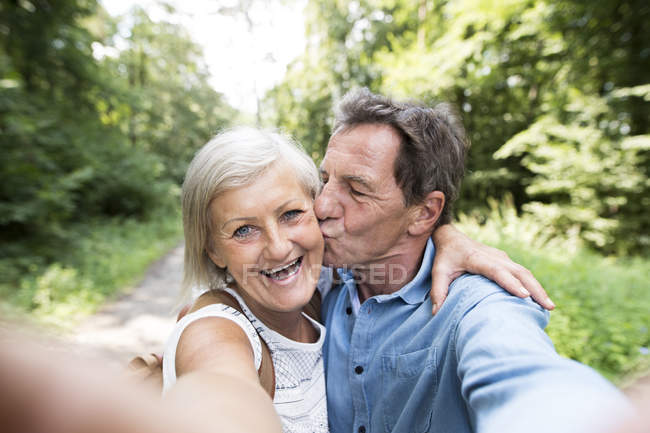 Active cute senior couple kissing and taking selfie in park — Stock Photo