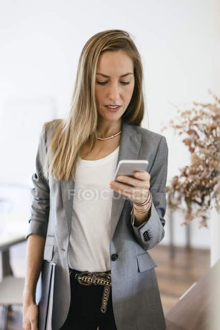 Donna di affari che controlla i messaggi sul suo smart phone, guardando preoccupato — Foto stock