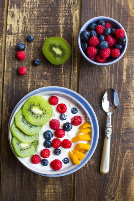 Vista superiore di yogurt con mirtilli, kiwi, mango e lamponi — Foto stock