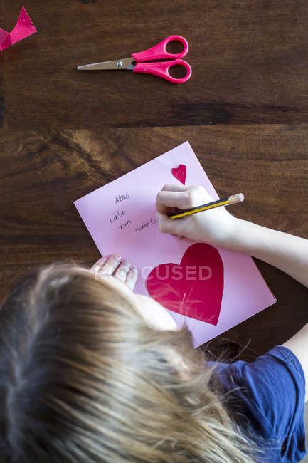Girl writing on mother day card — Stock Photo