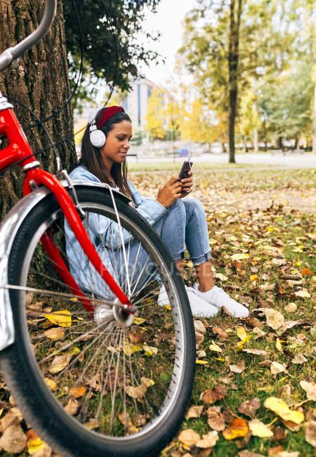 Mujer joven escuchando música con su smartphone en el parque - foto de stock