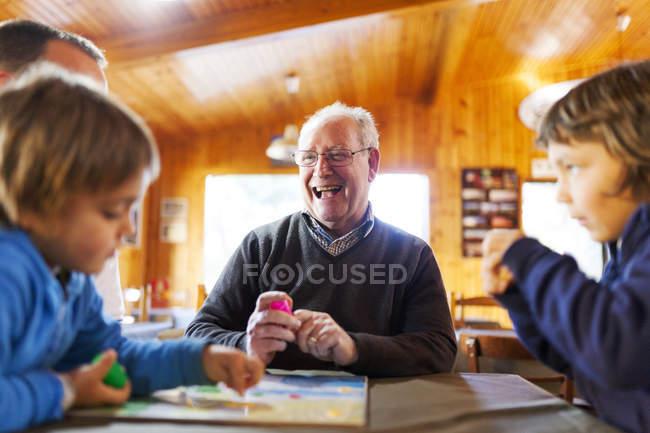 Jugar ludo con el hijo y nietos en la casa del abuelo - foto de stock