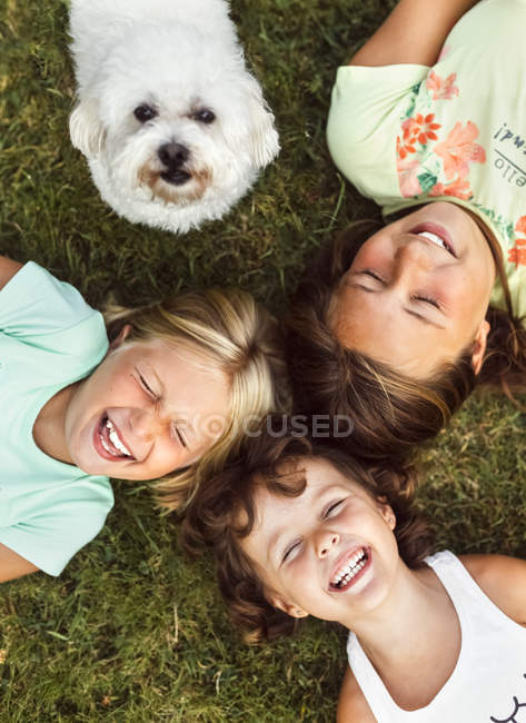 Three little girls with a puppy lying on the grass — Stock Photo