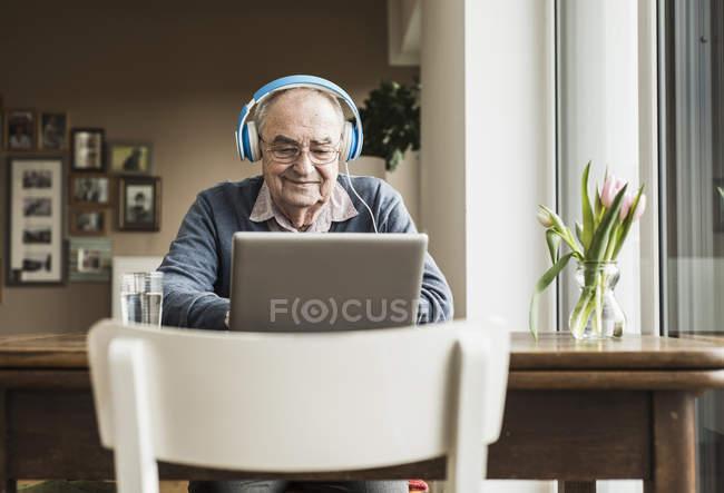 Senior homme avec ordinateur portable et un casque à la maison — Photo de stock