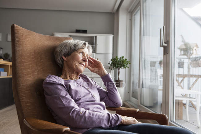 Portrait of senior woman sitting on armchair at home looking through window — Stock Photo