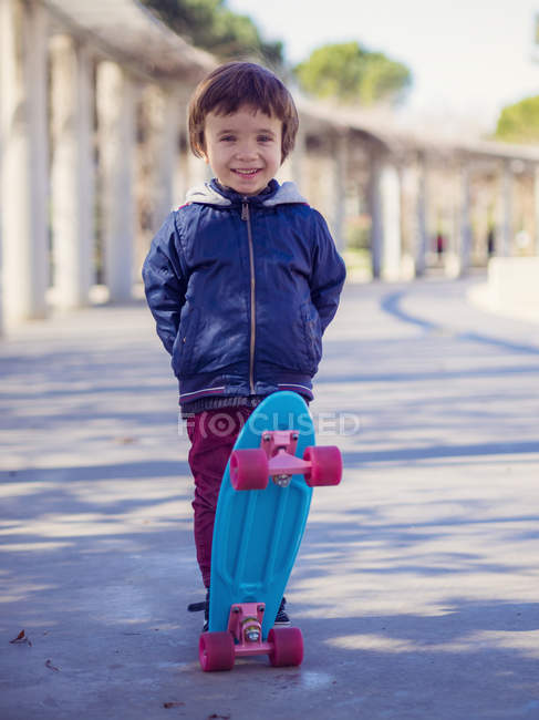 Portrait of smiling little boy with skateboard — Stock Photo