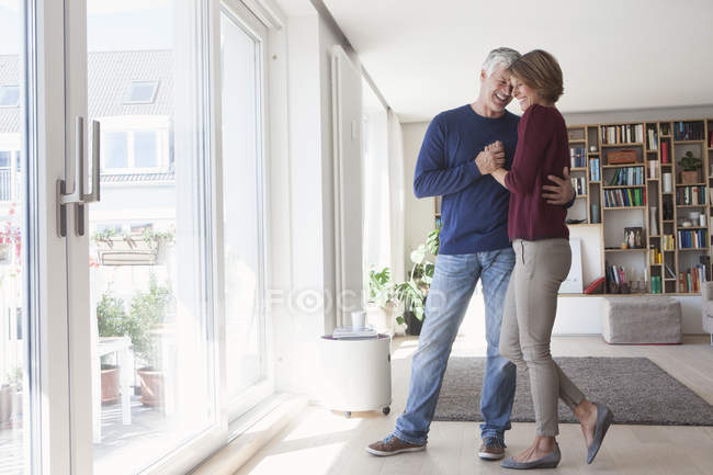 Laughing mature adult caucasian couple hugging at home — Stock Photo