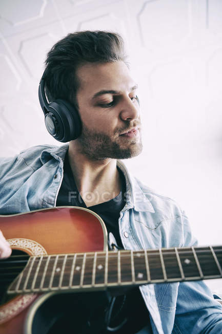 Young man wearing headphones and playing guitar — Stock Photo