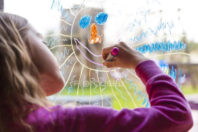 Vue recadrée de fille peinture soleil sur vitre — Photo de stock