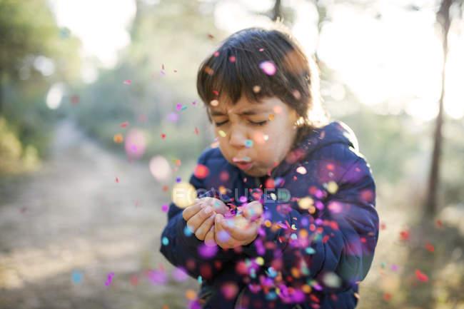 Маленький хлопчик дме конфетті в повітря — стокове фото