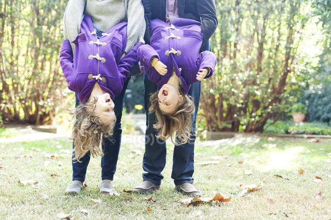 Two screaming little girls holding upside down by her parents — Stock Photo