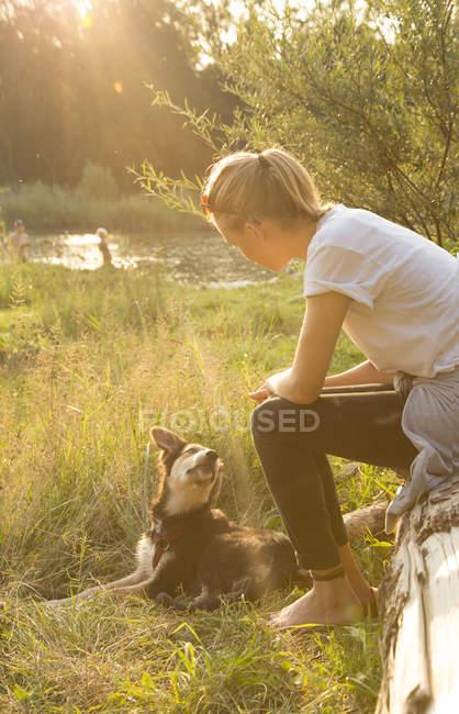 Giovane donna che si distende con il suo cane in natura al tramonto — Foto stock
