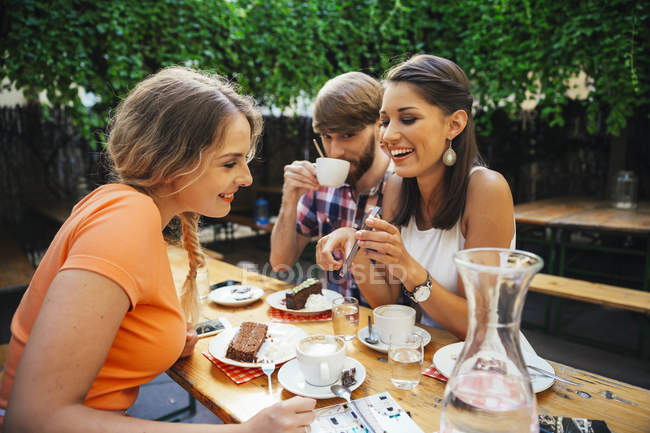 Friends with cell phone sitting outdoors having coffee and cake — Stock Photo