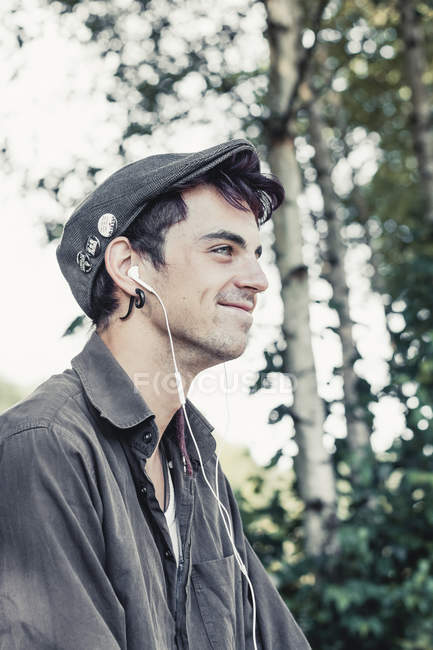 Smiling young man with cap listening music with earphones — Stock Photo
