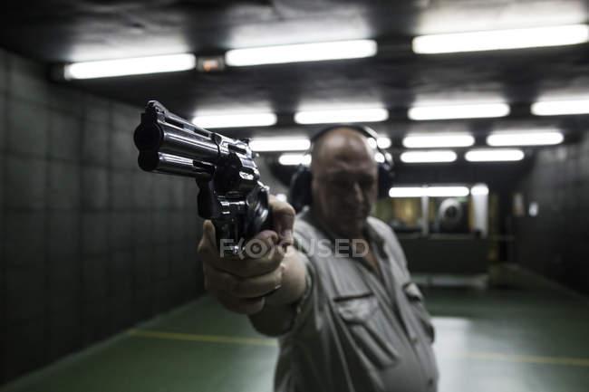 Homem com protecters de audiência, com o objetivo com um revólver em um campo de tiro indoor — Fotografia de Stock