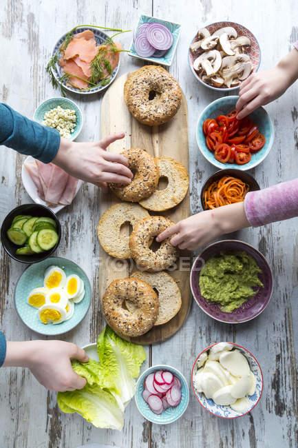 Colazione, ciambelle (bagels), verdure, salmone e prosciutto, mani prendendo ingredienti — Foto stock