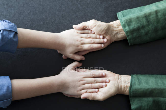 Grandmother and granddaughter holding hands, close-up — Stock Photo
