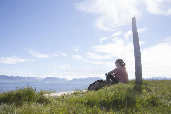 Islândia, alpinista, repousando sobre um prado olhando a vista — Fotografia de Stock