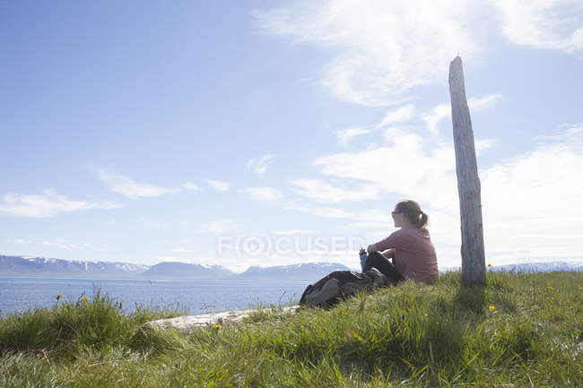 Iceland, hiker resting on a meadow looking at view — Stock Photo