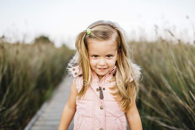 Bambina sveglia caucasica divertirsi in erba verde lunga — Foto stock