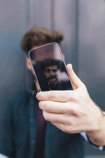 Handsome young male hipster making selfie on smartphone — Stock Photo