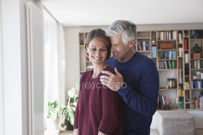 Happy mature adult caucasian couple hugging at home — Stock Photo