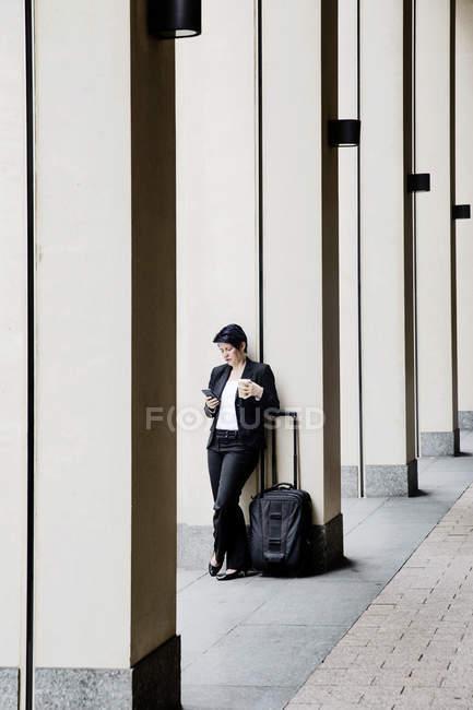 Деловая женщина с тележкой с помощью смарт-телефона, попивая кофе — стоковое фото