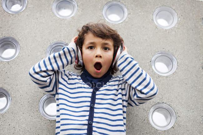 Портрет изумленного мальчика, слушающего музыку в наушниках — стоковое фото